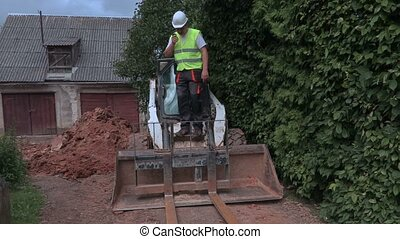 Worker talking on walkie talkie near tractor