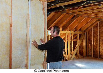 Worker thermally insulating a house attic using mineral wool...