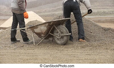 Worker throwing gravel into the cart - Worker throwing...