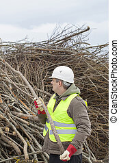 Worker throws wooden branches on heap