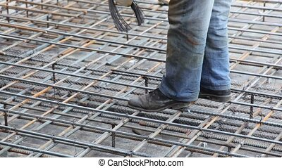 Worker tightens wire on metal carcass, only feet are visible...