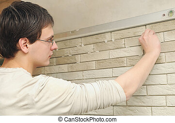 worker tiler at work - young worker tiler laying a tile on...
