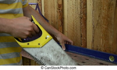 constructor worker man take various tools from toolbox on table on background of wooden plank wall.