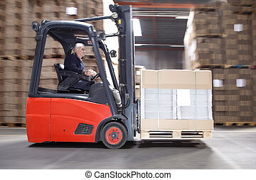Worker Transporting Stock On Forklift - Side view of male...