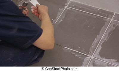 Worker troweling joints between tiles on floor