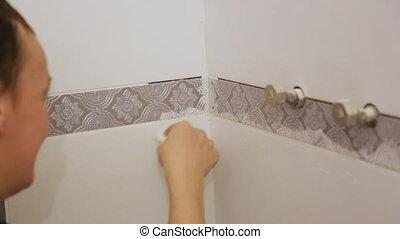 Worker troweling joints between tiles on wall