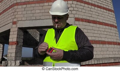 Worker trying to ignite cigarette