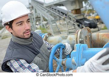 Worker turning wheel on machine
