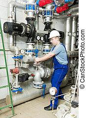 worker turns a valve