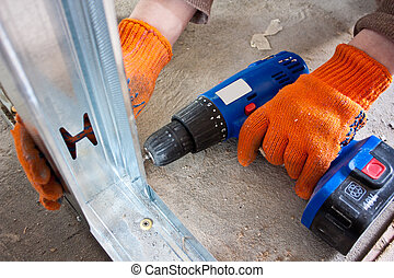 worker turns drywall screwdriver