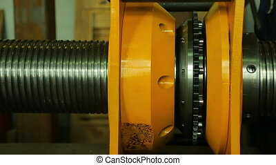 Worker twists metal part with thread in yellow press, by hand.