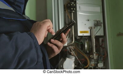 Worker typing on smartphone against gas-fire boiler