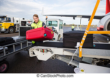 Worker Unloading Luggage From Conveyor Attached To Airplane