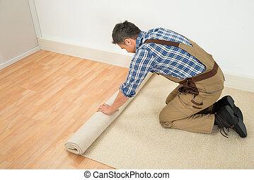 Worker Unrolling Carpet On Floor