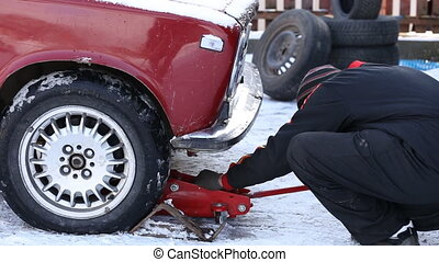 Worker untwists wheel - worker unscrews the wheel of the car...