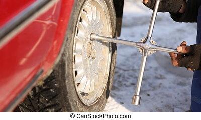 Worker untwists wheel - worker unscrews the wheel of the car...