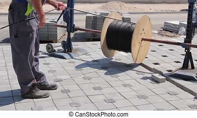 Worker unwinds cable spool. - Electrician is unwinding cable...