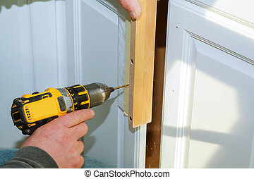 Worker use drill to repair furnitureand drills the cabinet door