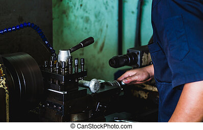 worker use lathe machine to product in workshop