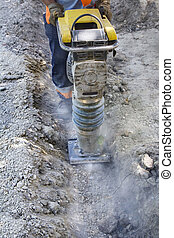 Worker uses compactor to firm soil at worksite
