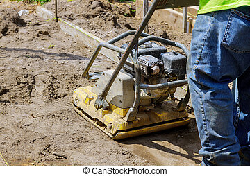 Worker uses compactor to vibratory hammer power tool at ...