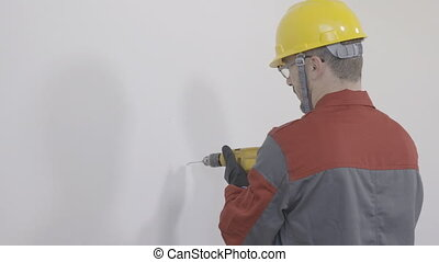 Worker using a drilling machine