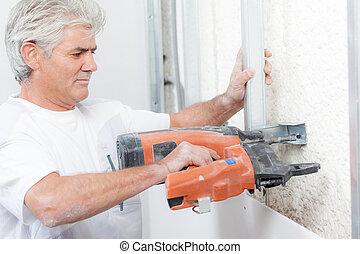 Worker using a nail gun