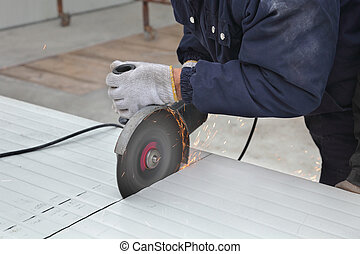 Worker using angle grinder, construction site