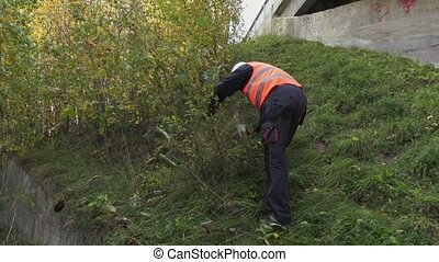 Worker using ax at outdoors near bushes