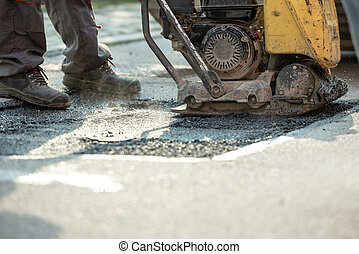 Worker using compactor to finish patching bump in the road