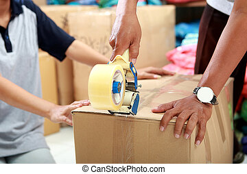 worker using duck tape for packing product into a box -...