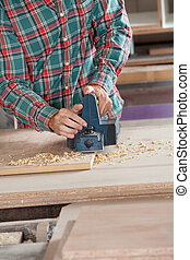 Worker Using Electric Planer On Wood