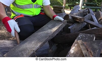 Worker using hammer near wooden boards