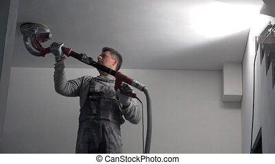 Worker using hand polishing machine to polish plasterboard...