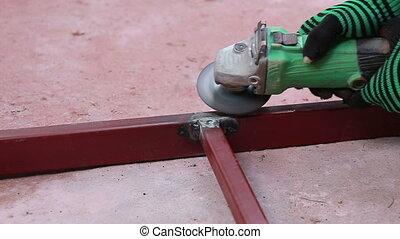 Worker using industrial grinder scrub steel