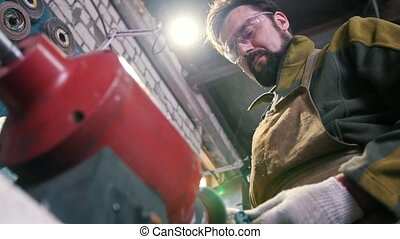 Worker using industrial grinding saw, rear view