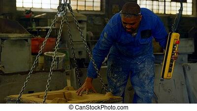 Worker using overhead crane in foundry workshop 4k - Worker ...