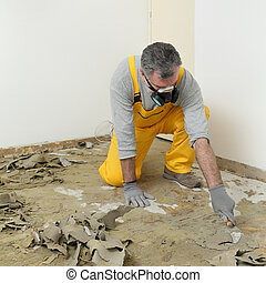 Worker using putty knife for cleaning floor - Adult worker ...