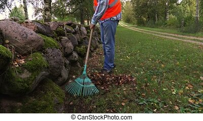 Worker using rake on grass