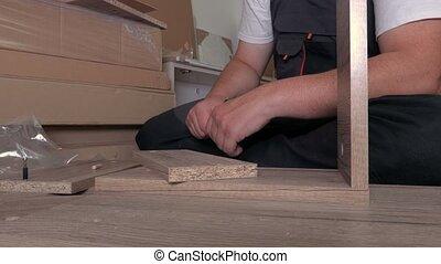 Worker using screwdriver on furniture detail