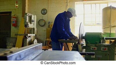 Worker using sharpening machine in foundry workshop 4k - ...