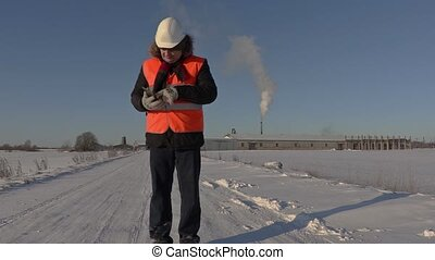 Worker using tablet and walking away to the factory