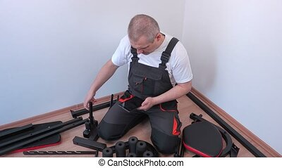 Worker using tablet near exercise machine components