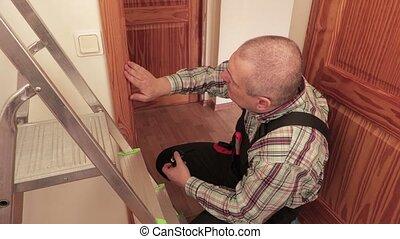 Worker using tape measure near door frames