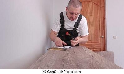 Worker using tape measure near furniture