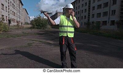 Worker using walkie talkie and keeping drone