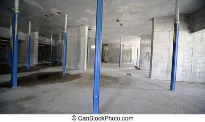 Worker walk inside dark unfinished room at construction site