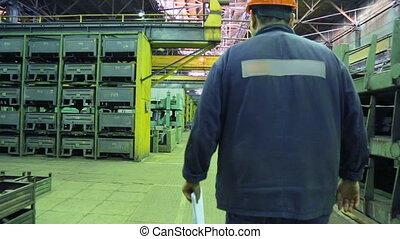 Worker walking along a walkway in a machine works