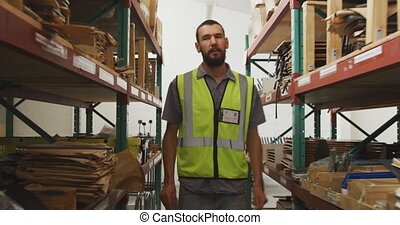 Worker walking between two shelves - Front view of an ...
