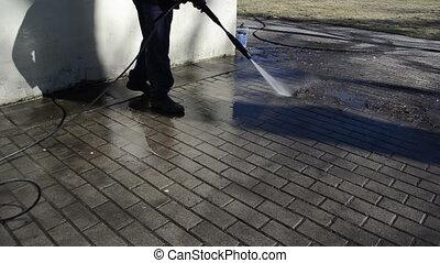 man washes yard tiles.